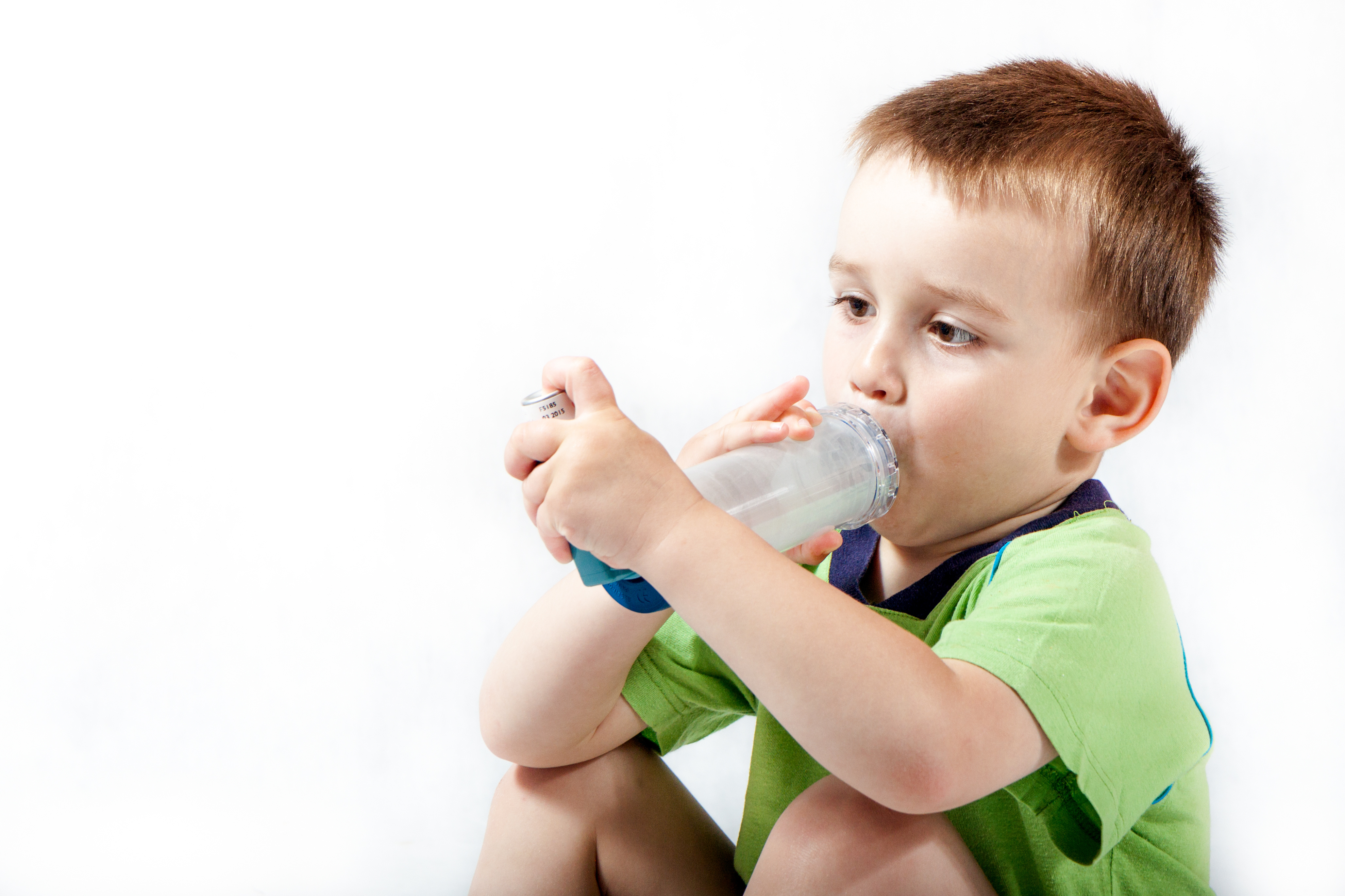 Little boy using inhaler for asthma isolated on white background